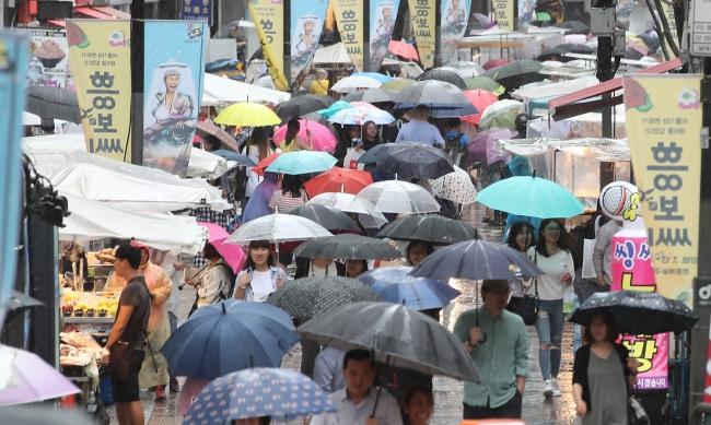 장마철에는 식중독, 알레르기 질환 등을 조심해야 한다. 에어컨, 보일러를 켜 습도를 낮추면 곰팡이 등의 번식을 막는데 도움이 된다. 외국인 관광객을 위한 '서울 썸머세일'이 시작된 지난 1일 오후 장맛비 속에서도 서울 중구 명동 상점가를 찾은 관광객들과 시민들. [연합뉴스]