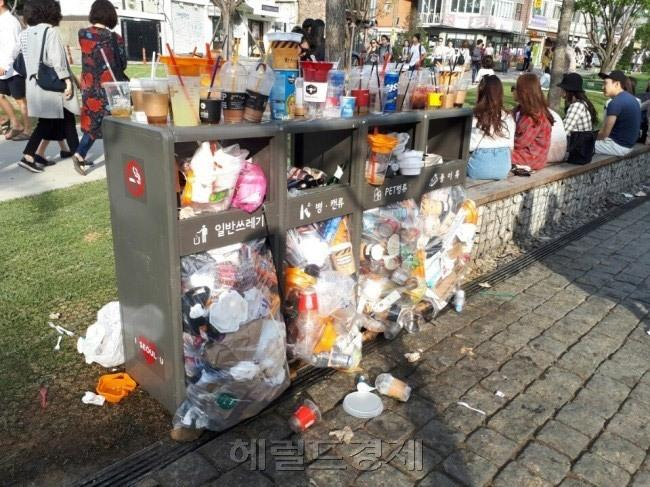 서울 시내 한 거리. 일회용컵 등 시민들이 버린 쓰레기로 쓰레기통이 포화상태가 됐다. 여름철에는 아이스음료 소비가 많아지면서 일회용컵 양이 급격히 늘어나고 악취 등 환경 문제도 심각해지고 있다.