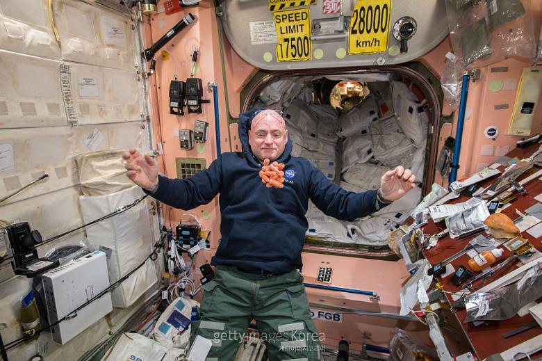 2015년 4월 19일 미국 항공우주국(NASA) 소속 우주비행사 스콧 켈리가 국제우주정거장(ISS)에 머물며 당근을 쳐다보고 있다. [게티이미지 제공]