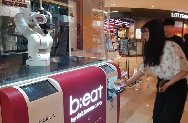 지난 4일 오후 서울 잠실 롯데월드몰을 찾은 방문객들이 건물 3층에 위치한 로봇카페 '비트'를 이용하고 있다. '비트'는 로봇 바리스타가 커피를 제조하는 이색 무인 카페다.